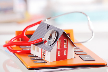 37247472 - conceptual simple model house with stethoscope on top of an orange calculator device placed on white table.